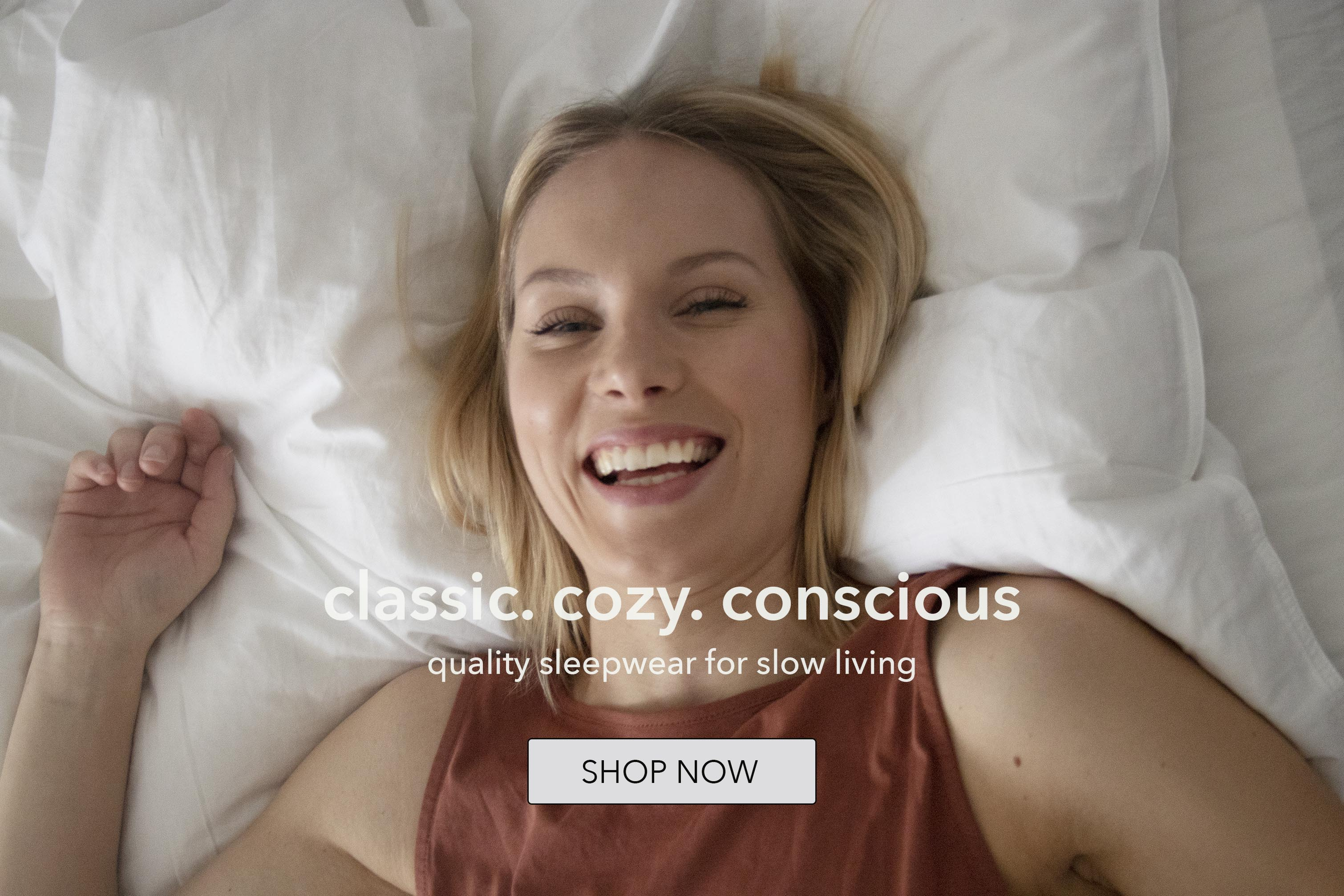 Woman laying in bed, smiling, in a Backdrop Nightgown from The Sleepy Collection